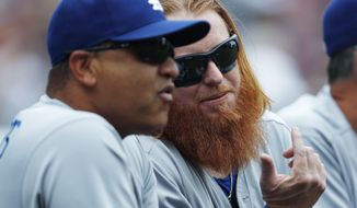 Los Angeles Dodgers third baseman Justin Turner, right, confers with manager Dave Roberts as they look on from the dugout rail in the first inning of a baseball game against the Colorado Rockies Sunday, Oct. 1, 2017, in Denver. (AP Photo/David Zalubowski)
