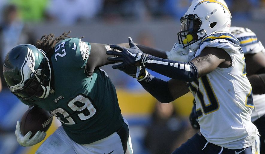 Philadelphia Eagles running back LeGarrette Blount, left, gets a hand on the face mask of Los Angeles Chargers defensive back Desmond King (20) as he runs during the second half of an NFL football game Sunday, Oct. 1, 2017, in Carson, Calif. (AP Photo/Mark J. Terrill)