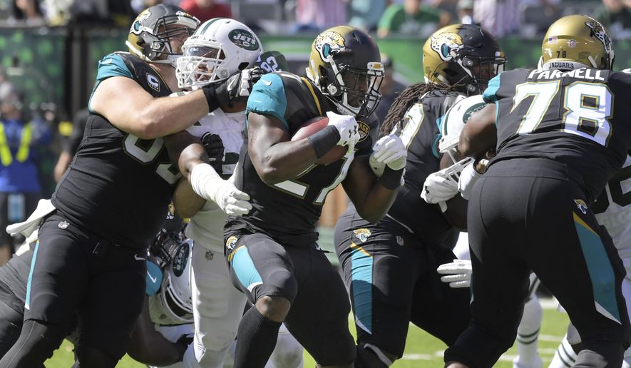Jacksonville Jaguars' Leonard Fournette, center, runs the ball during the first half of an NFL football game against the New York Jets, Sunday, Oct. 1, 2017, in East Rutherford, N.J. (AP Photo/Bill Kostroun)