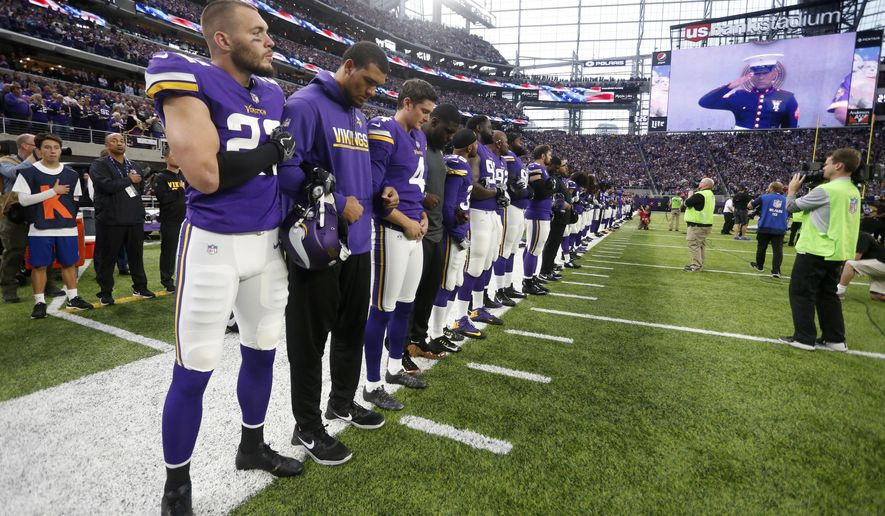 Minnesota Vikings players lock arms during the playing of the national anthem before an NFL football game against the Detroit Lions, Sunday, Oct. 1, 2017, in Minneapolis. (AP Photo/Bruce Kluckhohn)