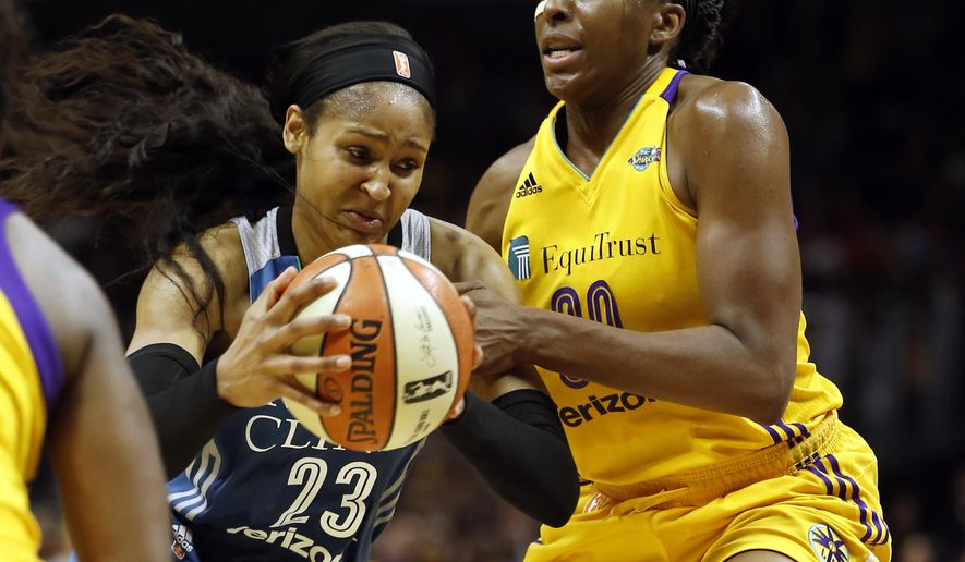 Minnesota Lynx forward Maya Moore, left, drives to the basket against Los Angeles Sparks forward Nneka Ogwumike during the first half in Game 4 of the WNBA basketball finals, Sunday, Oct. 1, 2017, in Los Angeles. (AP Photo/Alex Gallardo)