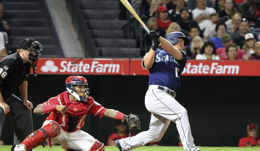 Seattle Mariners' Kyle Seager connects on a three-run home run as Los Angeles Angels catcher Martin Maldonado watches in the eighth inning of a baseball game in Anaheim, Calif., Saturday, Sept. 30, 2017. (AP Photo/Reed Saxon)