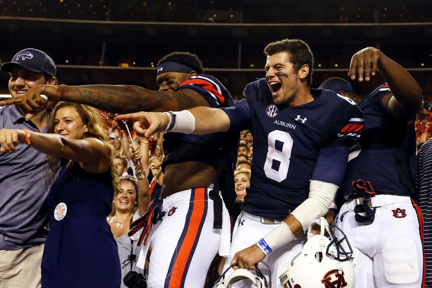 Auburn quarterback Jarrett Stidham (8) and Auburn wide receiver Kyle Davis (11) celebrate with fans after defeating Mississippi State 49-10 in an NCAA college football game, Saturday, Sept. 30, 2017, in Auburn, Ala. (AP Photo/Butch Dill)