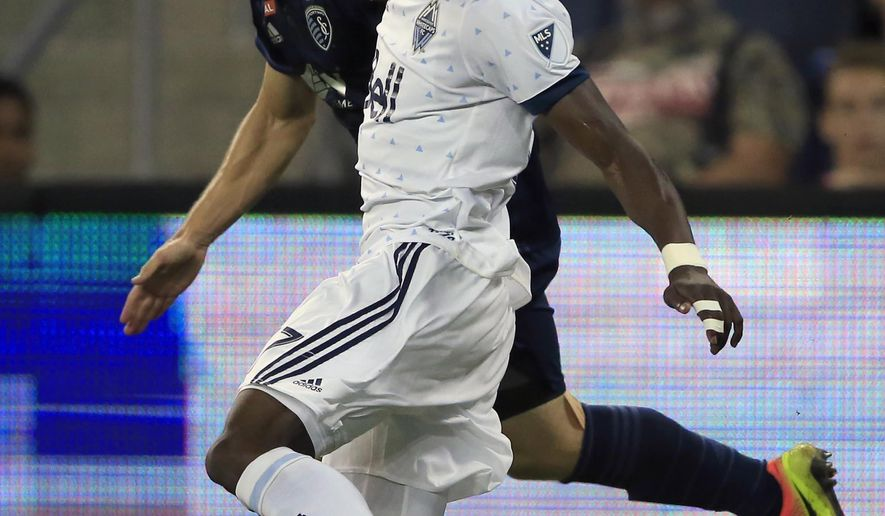 Vancouver Whitecaps forward Alphonso Davies, front, works the ball against Sporting Kansas City defender Seth Sinovic, back, during the first half of an MLS soccer match in Kansas City, Kan., Saturday, Sept. 30, 2017. (AP Photo/Orlin Wagner)