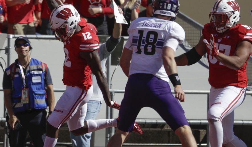 Wisconsin's Natrell Jamerson scores in front of Northwestern's Clayton Thorson (18) after intercepting a pass during the second half of an NCAA college football game Saturday, Sept. 30, 2017, in Madison, Wis. Wisconsin won 33-24. (AP Photo/Morry Gash)