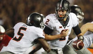 Oklahoma State quarterback Mason Rudolph hands off to running back Justice Hill in the second quarter in an NCAA college football game against Texas Tech, Saturday, Sept. 30, 2017, in Lubbock, Texas. (Mark Rogers/Lubbock Avalanche-Journal via AP)