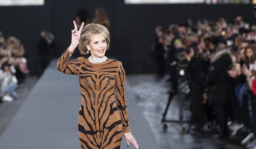 Actress Jane Fonda gestures a peace sign as she wears a creation for L'Oreal Spring/Summer 2018 ready-to-wear fashion collection presented in Paris, Sunday, Oct .1, 2017. (AP Photo/Kamil Zihnioglu)