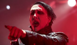 """FILE - In this Aug. 2, 2015 file photo, Marilyn Manson performs in concert during the """"End Times Tour 2015"""" at the Susquehanna Bank Center, in Camden, N.J. Manson's representative said Saturday, Sept. 30, 2017, that the singer was injured in a mishap on stage during a New York City performance and taken to a hospital. (Photo by Owen Sweeney/Invision/AP, File)"""