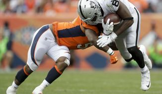 Oakland Raiders tight end Jared Cook, right, is tackled by Denver Broncos inside linebacker Todd Davis during the second half of an NFL football game Sunday, Oct. 1, 2017, in Denver. (AP Photo/Joe Mahoney)