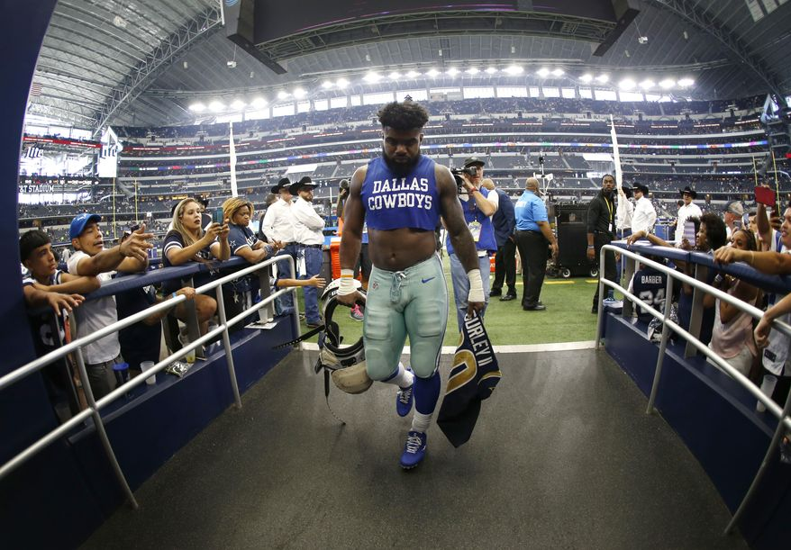 Dallas Cowboys running back Ezekiel Elliott (21) walks off the field holding the jersey of Los Angeles Rams running back Todd Gurley after their NFL football game, Sunday, Oct. 1, 2017, in Arlington, Texas. (AP Photo/Ron Jenkins)