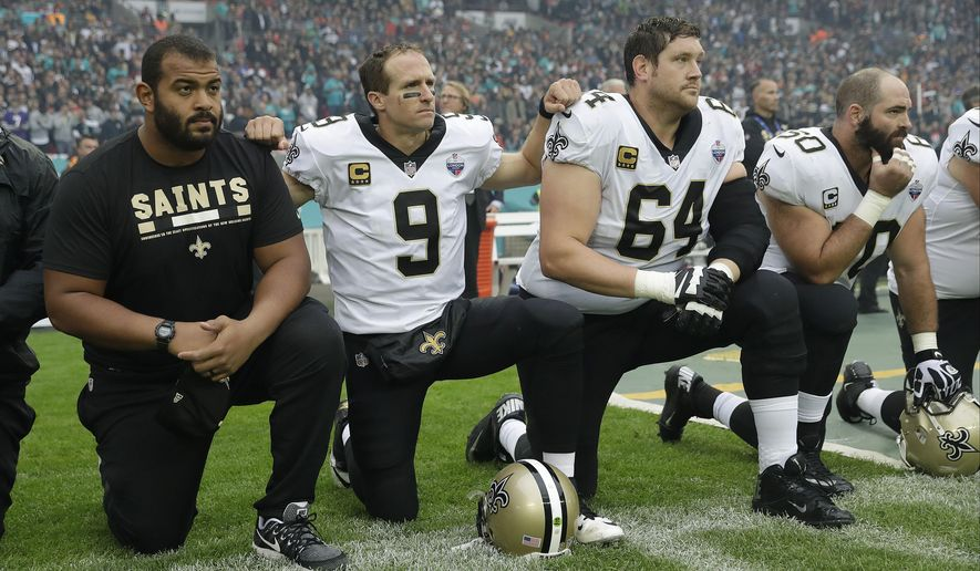 New Orleans Saints quarterback Drew Brees (9) kneels down with teammates before the U.S. national anthem was played ahead of an NFL football game against Miami Dolphins at Wembley Stadium in London, Sunday Oct. 1, 2017. Saints players then stood when the anthem was played. (AP Photo/Tim Ireland)