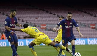 Barcelona's Lionel Messi, right, is challenged by Las Palmas' Mauricio Lemos, center, during the Spanish La Liga soccer match between Barcelona and Las Palmas at the Camp Nou stadium in Barcelona, Spain, Sunday, Oct. 1, 2017. Barcelona's Spanish league game against Las Palmas is played without fans amid the controversial referendum on Catalonia's independence. (AP Photo/Manu Fernandez)