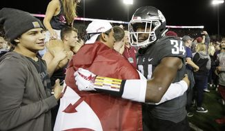 Washington State safety Jalen Thompson (34) celebrates with fans after his team won an NCAA college football game against Southern California in Pullman, Wash., Friday, Sept. 29, 2017. Washington State won 30-27. (AP Photo/Young Kwak)