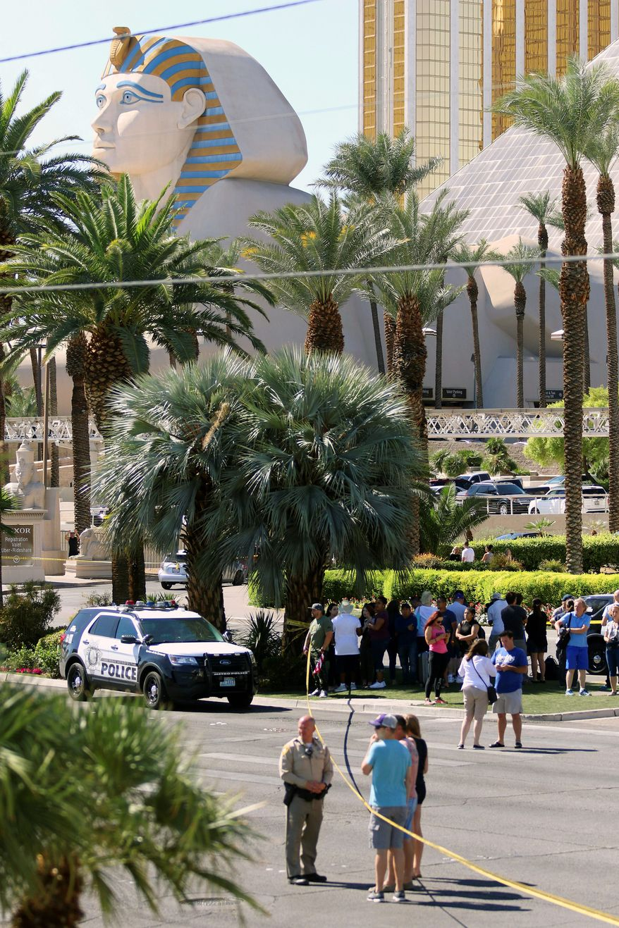 People gathered Monday at the scene of the mass shooting on the Las Vegas Strip the night before. Authorities are investigating the gunman's motive for the attack and the types of weapons used. (Associated Press)
