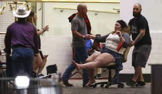 One of the hundreds of people wounded is moved outside the Tropicana on Sunday. Strangers sped victims to hospitals, which filled to capacity. (Associated Press)