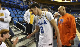 UCLA's Lonzo Ball (2) greets his brother LaMelo Ball, left, after scoring 20 points in their 114-77 win over Long Beach State at an NCAA college basketball game in Los Angeles, Sunday, Nov. 20, 2016. Behind Lonzo is his brother LiAngelo Ball and father LaVar Ball, right. (AP Photo/Michael Owen Baker) **FILE**