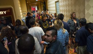 People are searched by Las Vegas police at the Tropicana Las Vegas during an active shooter situation on the Las Vegas Strip on Sunday, Oct. 1, 2017. Multiple victims were being transported to hospitals after a shooting late Sunday at a music festival on the Las Vegas Strip. (Chase Stevens/Las Vegas Review-Journal via AP)