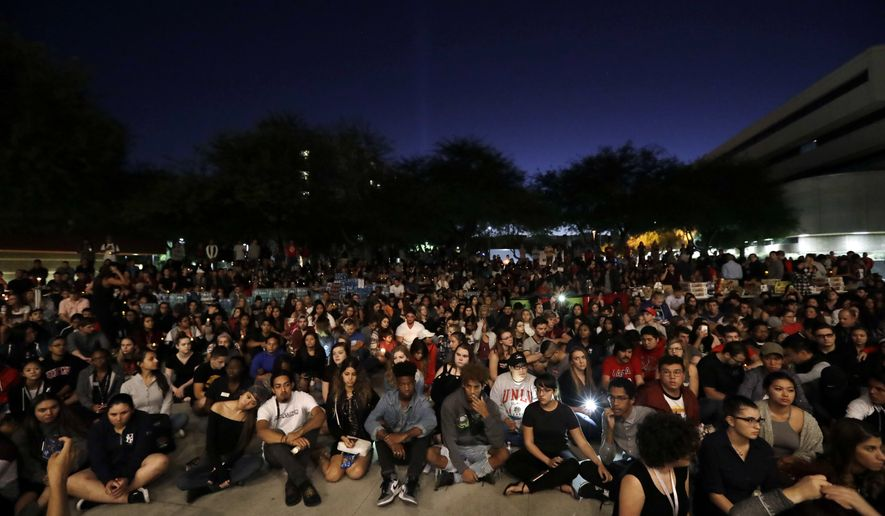Students from University of Nevada Las Vegas hold a vigil Monday, Oct. 2, 2017, in Las Vegas. A gunman on the 32nd floor of the Mandalay Bay casino hotel rained automatic weapons fire down on the crowd of over 22,000 at an outdoor country music festival Sunday. (AP Photo/Gregory Bull)