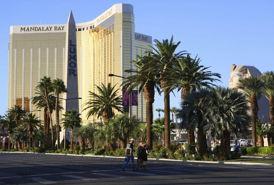 People walk near Mandalay Bay hotel-casino Monday, Oct. 2, 2017, in Las Vegas. A mass shooting occurred late night Sunday at a music festival on the Las Vegas Strip. (AP Photo/Ronda Churchill)
