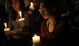 Natalynn Rivis, a student at University of Nevada Las Vegas, right, takes part in a vigil Monday, Oct. 2, 2017, in Las Vegas. A gunman on the 32nd floor of the Mandalay Bay casino hotel rained automatic weapons fire down on the crowd of over 22,000 at an outdoor country music festival Sunday. (AP Photo/Gregory Bull)