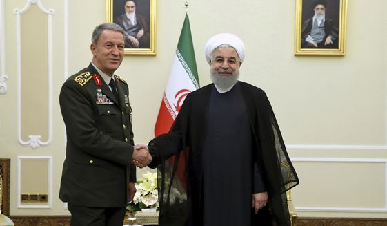 In this photo released by an official website of the office of the Iranian Presidency, President Hassan Rouhani, right, shakes hands with Turkey's Chief of Staff Gen. Hulusi Akar, in Tehran, Iran, Monday, Oct. 2, 2017. (Iranian Presidency Office via AP)