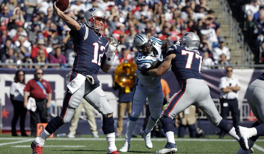 New England Patriots quarterback Tom Brady (12) passes under pressure from Carolina Panthers defensive end Mario Addison, center, being blocked by Patriots tackle Nate Solder (77) during the first half of an NFL football game, Sunday, Oct. 1, 2017, in Foxborough, Mass. (AP Photo/Steven Senne)