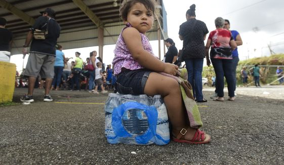 Kerialys Aldea de Jesus sits on bottled water at the Jose de Diego Elementary School where residents file FEMA forms for federal aid in the aftermath of Hurricane Maria in Las Piedras, Puerto Rico, Monday, Oct. 2, 2017. Even those happy with the federal aid effort for the U.S. territory's 3.4 million people said they resented President Donald Trump's tweets about some Puerto Ricans being lazy and ungrateful. (AP Photo/Carlos Giusti)