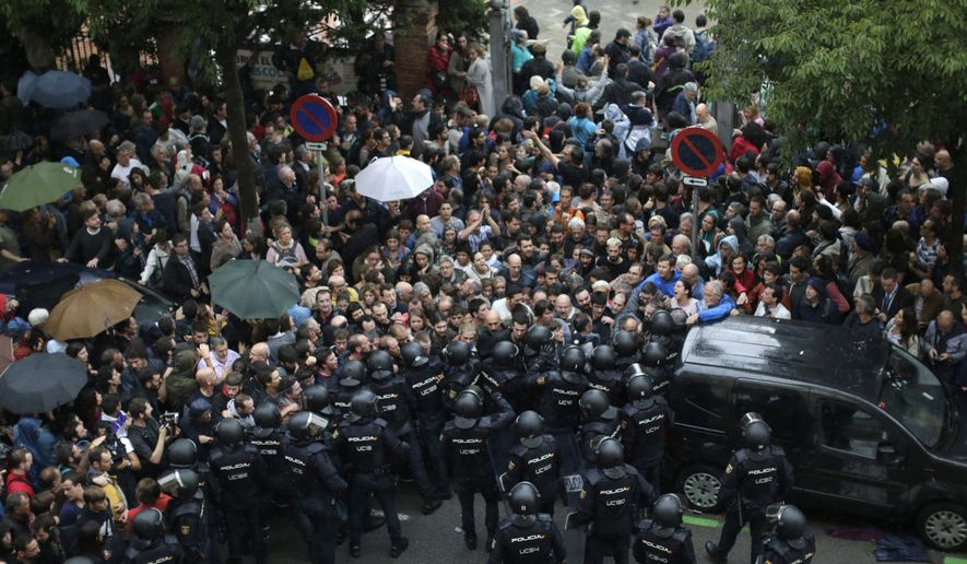 FILE, In this Sunday, Oct. 1, 2017 photo Spanish National Police prevents people from entering a voting site at a school assigned to be a polling station by the Catalan government in Barcelona, Spain. (AP Photo/Emilio Morenatti, File)
