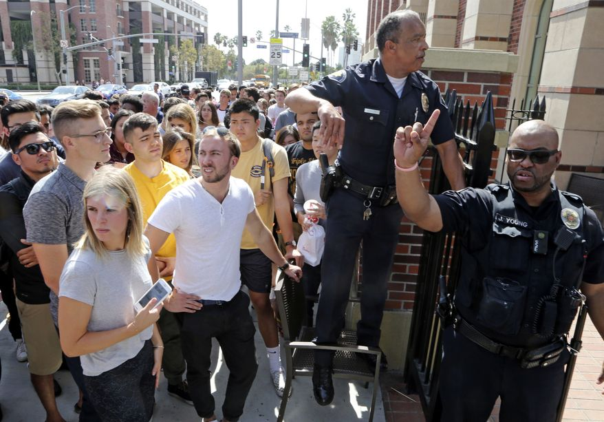 University police officers prepare to readmit students to retrieve belongings after they were escorted from a building at the University of Southern California while police made a floor-by-floor sweep after a report of shooting on the campus in downtown Los Angeles Monday, Oct. 2, 2017. Authorities said they found no evidence of a shooting on the campus and there is no danger to the university or the community. (AP Photo/Reed Saxon)