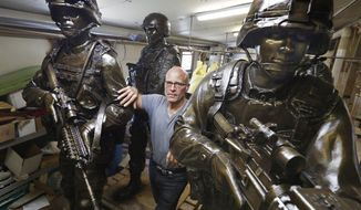 Alan Cottrill, a well-known Zanesville, Ohio sculptor, has been commissioned by the National Infantry Museum in Georgia to do nine 7-foot sculptures of combat soldiers for the Global War on Terror Memorial. Cottrill poses in his studio with some of the finished statues  on Thursday, September 21, 2017. (Fred Squillante/The Columbus Dispatch via AP)
