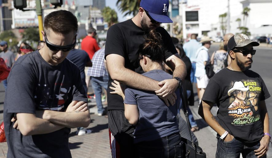 Reed Broschart, center, hugs his girlfriend Aria James on the Las Vegas Strip in the aftermath of a mass shooting at a concert Monday, Oct. 2, 2017, in Las Vegas. The couple, both of Ventura, Calif., attended the concert. (AP Photo/Marcio Jose Sanchez)