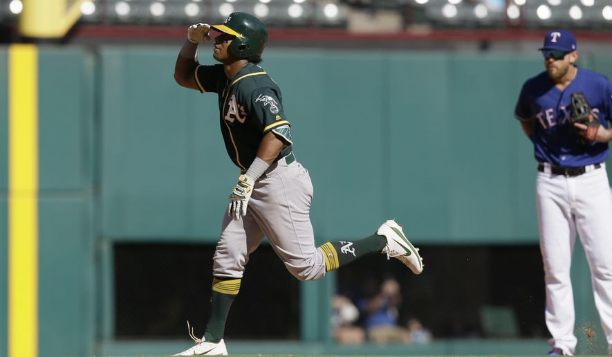 Oakland Athletics' Khris Davis salutes as he runs the bases after hitting a solo home run during the eighth inning of a baseball game against the Texas Rangers in Arlington, Texas, Sunday, Oct. 1, 2017. (AP Photo/LM Otero)