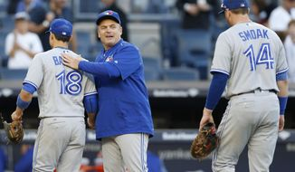 Toronto Blue Jays manager John Gibbons, center, congratulates his players, including  third baseman Darwin Barney (18) and first baseman Justin Smoak, after their victory over the New York Yankees in a baseball game in New York, Sunday, Oct. 1, 2017. (AP Photo/Kathy Willens)