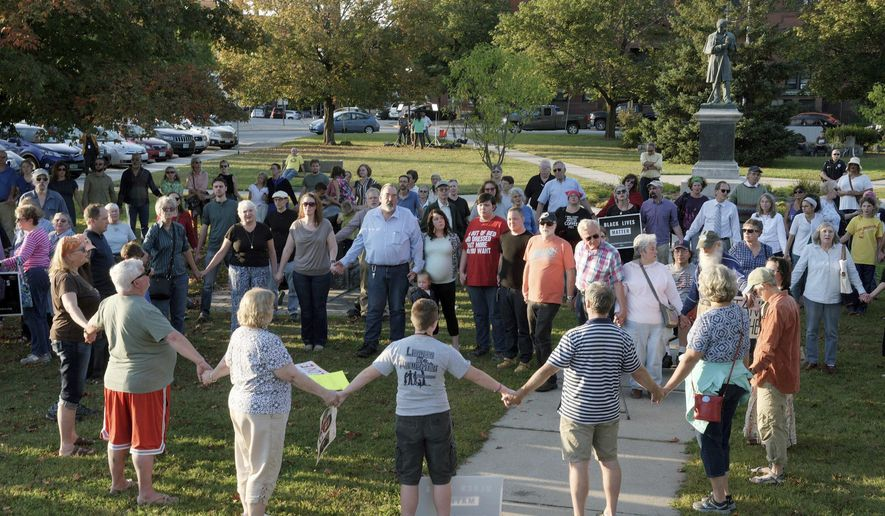 "FILE - In this Sept. 12, 2017, file photo, a chorus of ""We Shall Overcome"" rises from a gathering against racism in Broad Street Park in Claremont, N.H. The demonstration was inspired by violence in August against an 8-year-old biracial boy that occurred while he played with a group of teenagers outside his home. The incident has prompted people in the town to reflect and assess how it handles the issue of race in this mostly white community. (James M. Patterson/The Valley News via AP, File)"