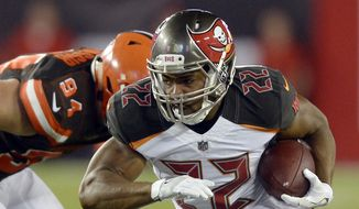 In this Aug. 26, 2017, file photo, Tampa Bay Buccaneers running back Doug Martin (22) eludes Cleveland Browns defensive end Carl Nassib (94) during the second quarter of an NFL preseason football game in Tampa, Fla. (AP Photo/Jason Behnken, File)