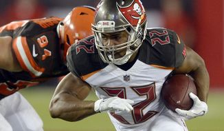FILE - In this Aug. 26, 2017, file photo, Tampa Bay Buccaneers running back Doug Martin (22) eludes Cleveland Browns defensive end Carl Nassib (94) during the second quarter of an NFL preseason football game in Tampa, Fla. Martin is back from a four-game suspension for violating the NFL's policy on performance enhancers. The question is how soon will he be ready to contribute to an offense that can use his help.(AP Photo/Jason Behnken, File)
