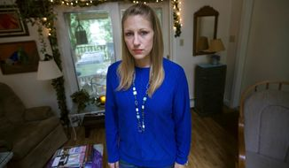 In this Sept. 22, 2017 photo, Julie Eldred poses for a photo in her Massachusetts home. Eldred, 29, tested positive for the opioid fentanyl less than two weeks after a court ordered her to refrain from drugs while on probation for larceny. She spent the next 10 days in jail until her lawyer could find her a bed in a treatment facility. On Monday, Oct. 2, 2017, Massachusetts' highest court will hear her case challenging the practice of ordering people with addiction to stay drug free as a condition of probation. (Jesse Costa/WBUR via AP)