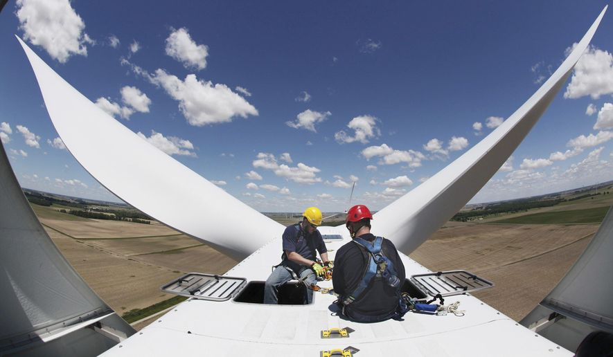 Jeremy Chenoweth (left) and Benjamin Werkowski of EDP Renewables work atop one of the 52 windmills the company operates in Paulding County, Ohio. The Timber Road II Wind Farm generates enough electricity to power 29,000 homes. (Associated Press/File)