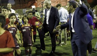 Italian soccer coach Carlo Ancelotti stand with Muslim, Christian and Jewish youth as part of the Assist for Peace, a coexistence group, in Jerusalem Monday, Oct. 2, 2017. Bayern Munich fired Ancelotti as coach on Thursday after the German team's heaviest Champions League group-stage defeat. (AP Photo/Mahmoud Illean)