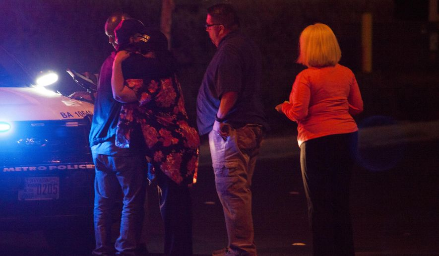 People embrace after arriving at Metro Headquarters to check on loved ones early Monday, Oct. 2, 2017, after a mass shooting at a music festival on the Las Vegas Strip Sunday. (Yasmina Chavez/Las Vegas Sun via AP)