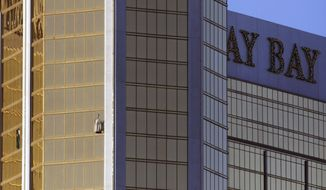 Drapes billow out of a broken window at the Mandalay Bay resort and casino Monday, Oct. 2, 2017, on the Las Vegas Strip following a deadly shooting at a music festival in Las Vegas. A gunman was found dead inside a hotel room. (AP Photo/Ronda Churchill)