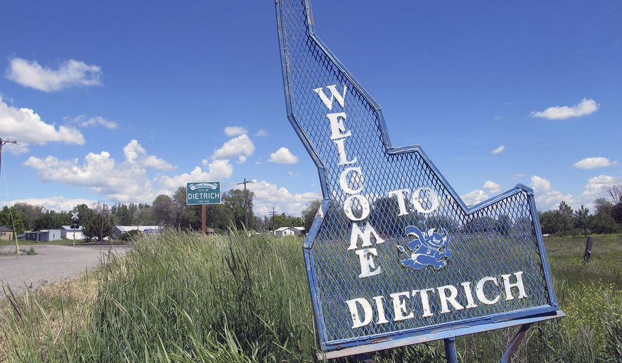 FILE - In this May 26, 2016, file photo, a sign welcomes residents and visitors to the tiny town in Dietrich, Idaho. The small community has faced national attention after a $10 million federal lawsuit was filed alleging the local school did nothing to prevent months of racist and sexual abuse of a disabled black teen. Lee Schlender, the victim's attorney, confirmed Monday, Oct. 2, 2017, that a monetary settlement had been reached with the Dietrich School District, but declined to share details regarding the amount and terms of the agreement. (AP Photo/Kimberlee Kruesi,File)
