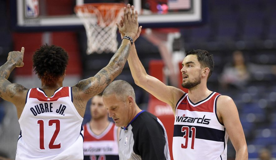 Washington Wizards guard Tomas Satoransky (31), of the Czech Republic, high-fives Kelly Oubre Jr. (12) during the second half of an NBA basketball exhibition game, Monday, Oct. 2, 2017, in Washington. (AP Photo/Nick Wass)
