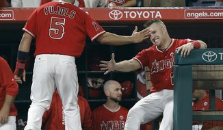 Los Angeles Angels' Albert Pujols (5) gets congratulations from Mike Trout after scoring on a single by C.J. Cron during the eighth inning of a baseball game against the Seattle Mariners in Anaheim, Calif., Friday, Sept. 29, 2017. (AP Photo/Alex Gallardo)