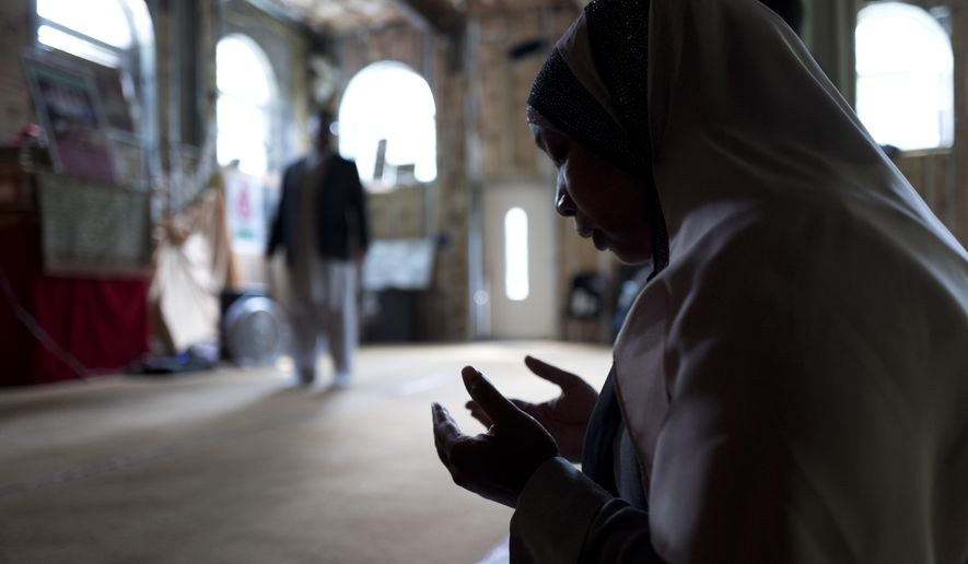 In this Sept. 7, 2017 photo, Tahirah Clark, an attorney for the Muslim enclave of Islamberg, prays in the community's mosque in Tompkins, N.Y. The enclave near the Catskill Mountains is dogged by terror accusations, many made on right-wing websites. Though police and analysts dismiss those accusations, they have persisted from the time the enclave was settled in the 1980s. (AP Photo/Mark Lennihan)