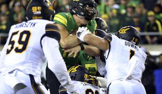 FILE - In this Saturday, Sept. 30 2017, file photo, Oregon's Justin Herbert, center, drives into the end zone for a touchdown against California's Quentin Tartabull, bottom, and Devante Downs during the first quarter of an NCAA college football game in Eugene, Ore. The Ducks are reeling from the aftermath of Saturday's game against California, with both quarterback Justin Herbert and running back Royce Freeman both injured in the victory (AP Photo/Chris Pietsch, File)