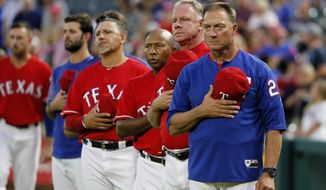 FILE- In this Thursday, Sept. 28, 2017, file photo, Texas Rangers manager Jeff Banister, right, staff and players stand during the playing of the national anthem before a baseball game against the Oakland Athletics in Arlington, Texas. (AP Photo/Tony Gutierrez, File)