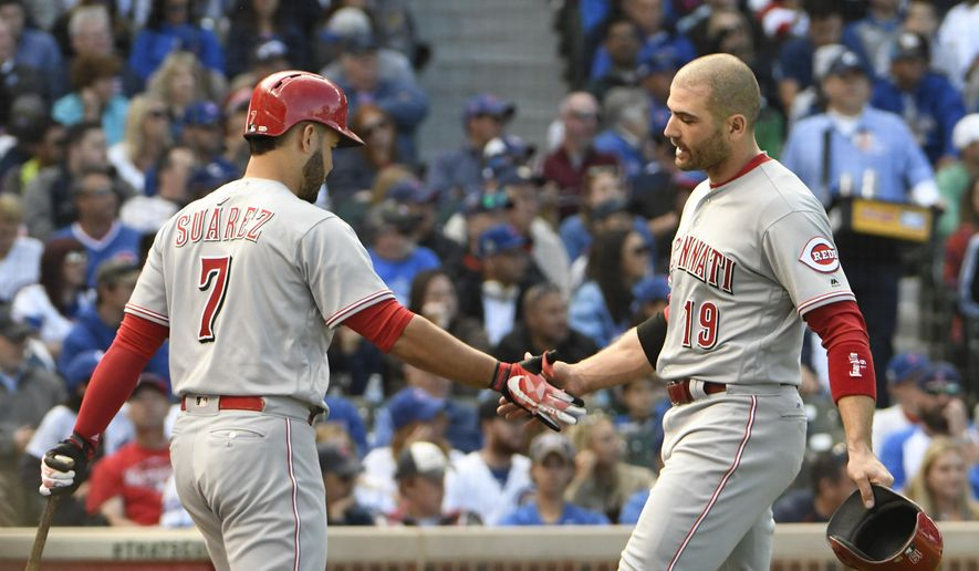 Cincinnati Reds' Joey Votto (19) is greeted by Eugenio Suarez (7) after scoring against the Chicago Cubs during the fourth inning of a baseball game, Sunday, Oct. 1, 2017, in Chicago. (AP Photo/David Banks)