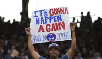 A Chicago Cubs fan holds a sign during the seventh inning of a baseball game against the Cincinnati Reds, Sunday, Oct. 1, 2017, in Chicago. (AP Photo/David Banks)