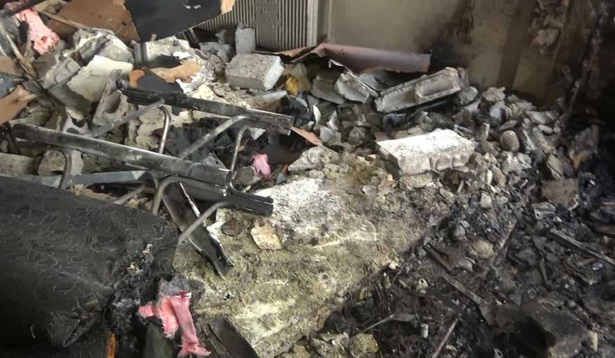 In this photo released by the Syrian official news agency SANA, shows damages after a suicide car bomber struck a police station in Damascus, Syria, Monday, Oct. 2, 2017. The Al-Ikhbariyeh TV station said one bomber detonated his vehicle in front of the police station and another one managed to enter the station in the capital's al-Midan neighborhood. (SANA via AP)